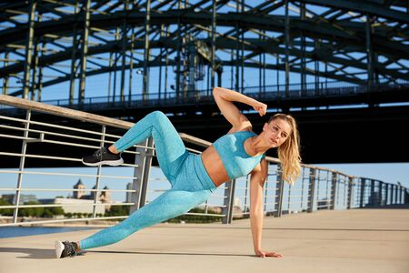 Young attractive woman makes early in the morning, with sunshine, outdoor, yoga, gymnastics workout in the city, on the river promenade in an urban environment
