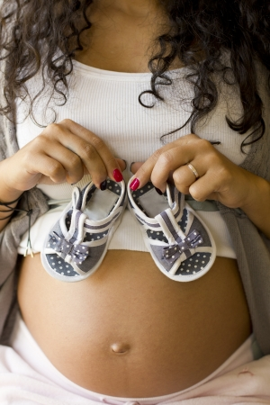 Pregnant woman holding baby shoes photo