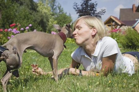 bluster: Young woman kissing with dog Stock Photo