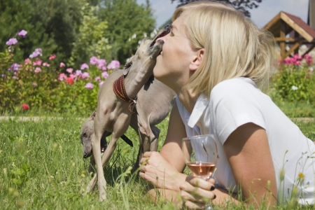 Young woman with dog and glass of wine Stock Photo