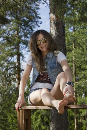 Beautiful woman sitting on wooden railing Stock Photo