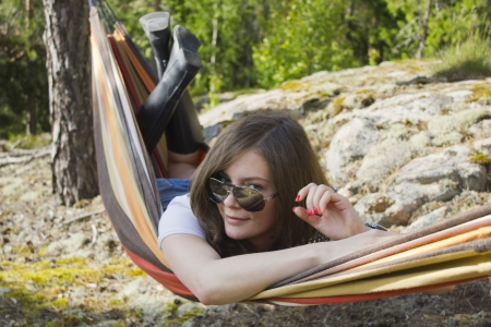 Beautiful young woman resting in hammock photo