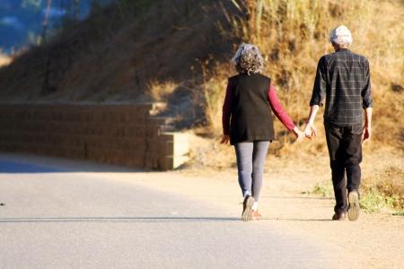 年配のカップルが手をつないで歩く 写真素材