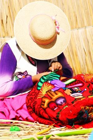 ウロス島、プーノ、ペルーの伝統的手作り工芸品を編むペルーの女性