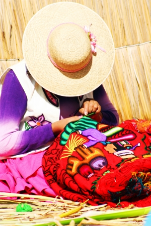 Peruvian women knitting traditional handmade craft in Uros Island, Puno, Peru