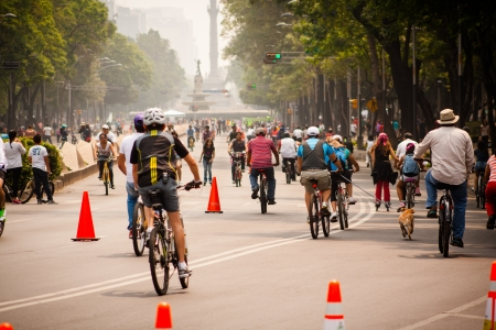 Photograph of cyclists at Mexico City. Angel behind.
