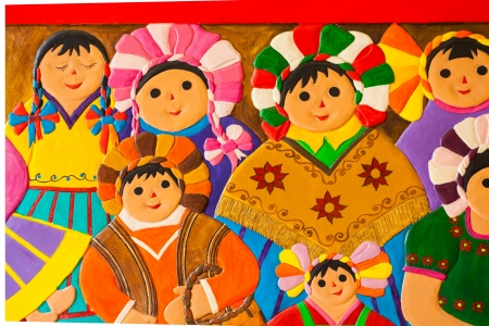Sculpture of a group of colorful mexican women on the wall
