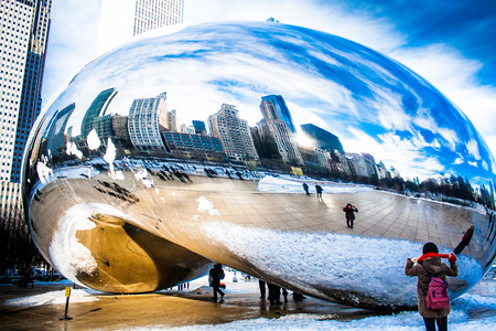 Skygate Bean covering by snow against high building towers and blue sky with unidentified visitors at Millenium Park 新闻类图片