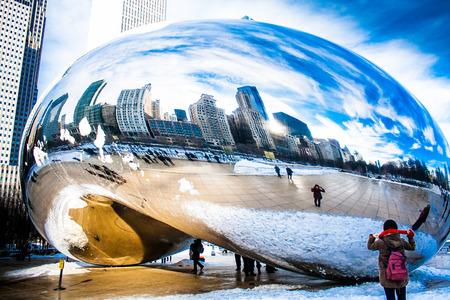 attach         â     â       ©: Skygate Bean cubriendo de nieve contra torres de edificios altos y cielo azul con visitantes no identificados en Millenium Park Editorial