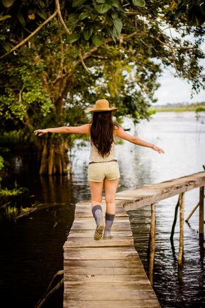 rio amazonas: Morena chica caminando en un puente en r�o de la selva amaz�nica Foto de archivo
