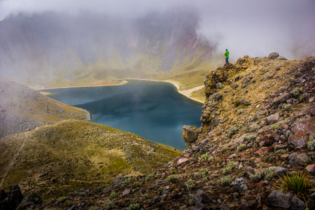Hiker man watching a lake in a foggy mountain photo