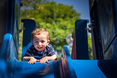 Happy smiling kid playing in the park playground photo