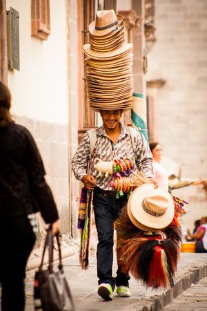 traje mexicano: Vendedor de sombreros tradicional riendo y caminando en San Miguel de Allende Guanajuato