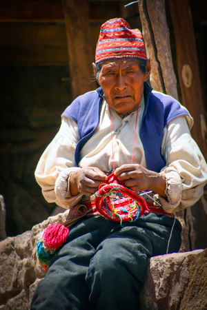 quechua indian: Old men knitting at taquile island in puno peru Stock Photo