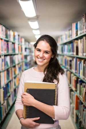 In the library - pretty female student with books working in a high school library. 版權商用圖片 - 34433451