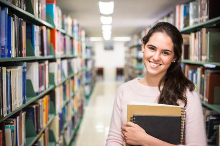 students: En la biblioteca - bastante estudiante con libros en una biblioteca de la escuela.
