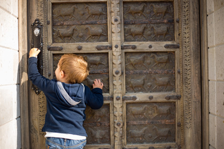 arrive: Cute little boy baby knocking on old door. Stock Photo