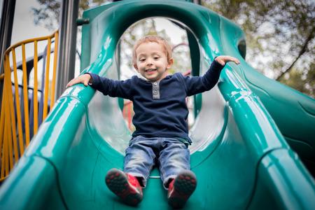 遊び場スライドに幸せな少年。