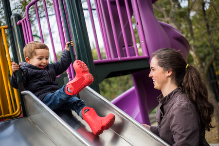 playground ride: happy little boy child and mother mom on the playground slide.
