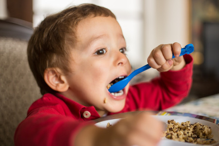 two persons only: Little boy child eating brown rice and quinoa.