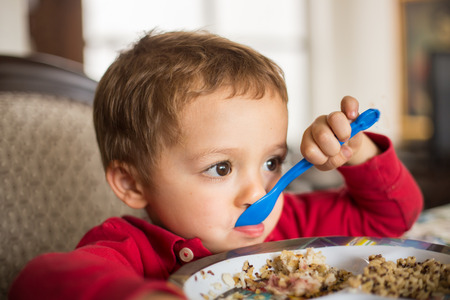 baby rice: Little boy child eating brown rice and quinoa.