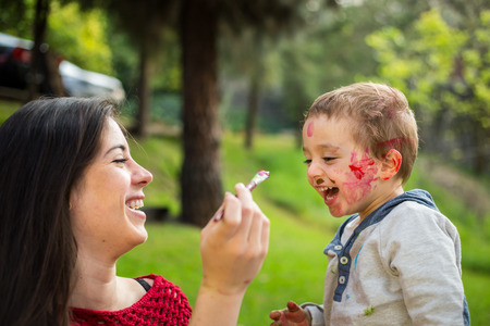 painting face: Happy mother painting her child�s face in the park. Stock Photo