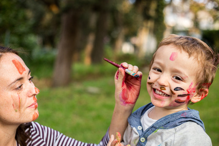 Happy mother painting her child´s face in the park. Banque d'images