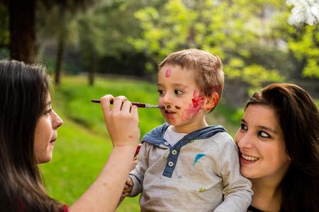 pintura en la cara: Madre feliz pintando su hijo? S cara en el parque.