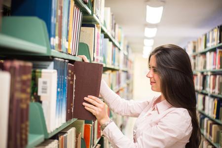 Dans la bibliothèque - étudiant jolie femme avec des livres de travail dans une bibliothèque de l'école secondaire. Banque d'images - 45986293