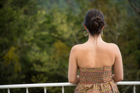 dark haired woman: Back view of dark haired woman watching the forest.