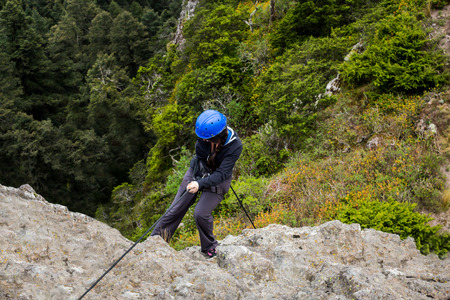 rappel: Climber rappelling on forested mountain slope  with the evergreen conifers.