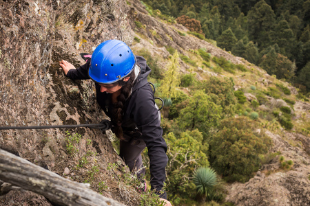 rappel: Rock climbing on forested mountain slope  with the evergreen conifers in a scenic summer landscape view.