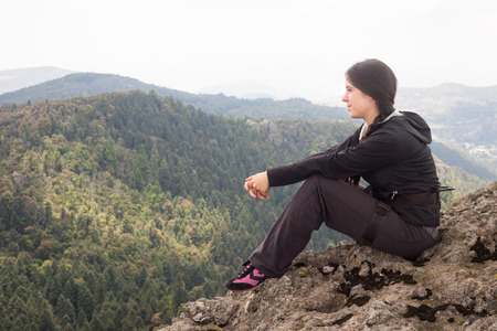forested: Climber resting on forested mountain slope  with the evergreen conifers. Stock Photo