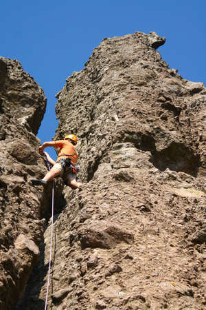 Young man rock climbing on a limestone wall. Banque d'images