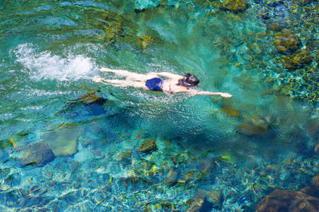 Young woman in blue swimsuit swimming and relaxing in the blue water sea. Top view, general plan with copy space.