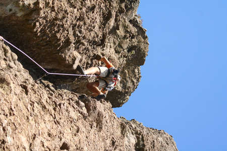 Young man rock climbing on a limestone wall. Banque d'images - 151564383