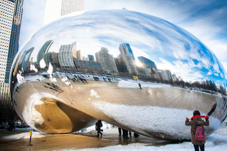 Skygate Bean covering by snow against high building towers and blue sky with unidentified visitors at Millenium Park Éditoriale