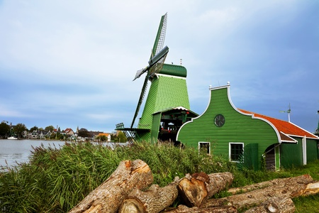 Dutch village with a green windmill and overcast skies after rain. photo