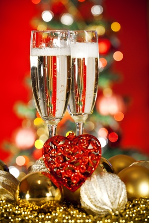 Two glasses of champagne, Christmas ornaments in the shape of hearts and light Christmas trees in the background. photo