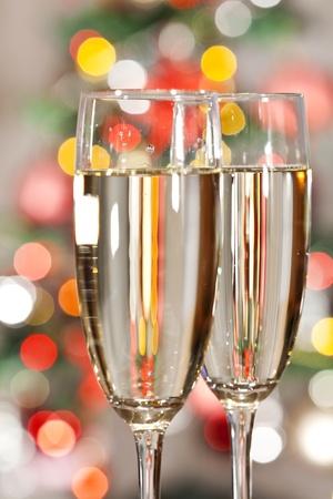 Zwei Gläser Champagner und Licht dem Weihnachtsbaum im Hintergrund.