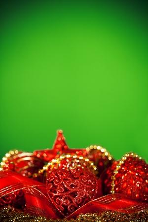iluminados: Oro y ornamentos rojos de la Navidad y fondo verde iluminada.