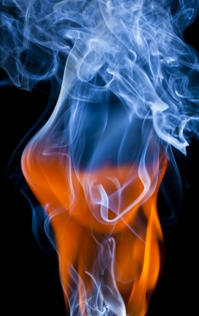 A great flame of fire and smoke in the swift black background.