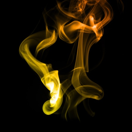 Elegant yellow and orange lines of smoke forming abstract figures.