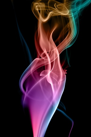 Colorful figures of smoke on a black background. Stock Photo