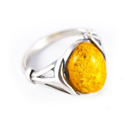 A large, old, silver ring with amber on white background. photo