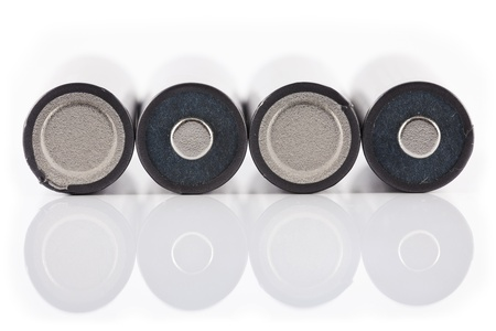 Four batteries placed on a white background with reflection. Stock Photo - 11980287