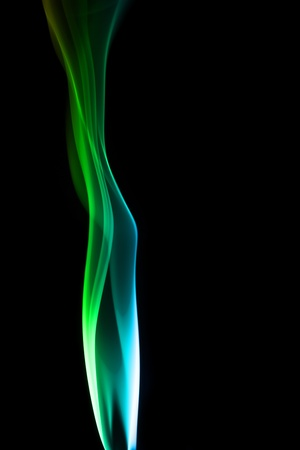 Green smoke rises up on a black background  photo