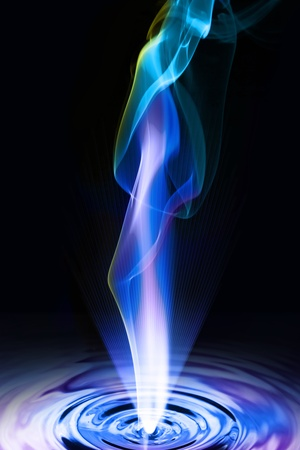 Smoke and light rays coming out of the blue liquid churned
