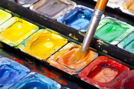 paintbox: Watercolors and a paintbrush dipped in orange  Stock Photo