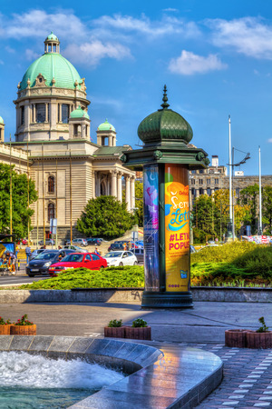 borne fontaine: SERBIA, BELGRADE - JULY 26: The Serbian Parliament from Nikola Pasic Square on July 26, 2017 in Belgrade. Serbian Parliament, fountain, city traffic and the citys post office are in the distance, HDR Image.